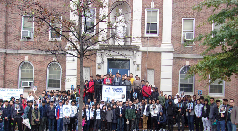 The entire group of participants in the front of the school, including Joshua's family members in the center of the photo