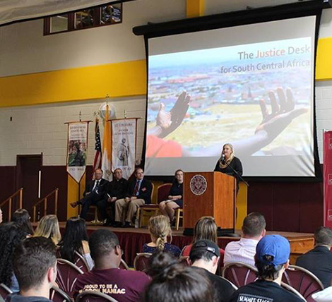 Jessica Dewhurst speaks to the Iona College campus community during her keynote speech. Seated on stage (l-r) are Dr. Joseph  Nyre, Iona College President, Br. Kevin Griffith, ERCBNA Province Leader, Carl Procario-Foley, Ph.D, Director of Iona College Mission and Ministry, and Iona College SGA President Hannah McGowan.