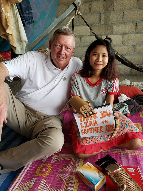 """Brother Rice Chicago alumnus and Chairman Emeritus of Love Without Boundaries, Paul Duggan poses with a recipient of one of Brother Rice's """"Helping Hands"""" in Cambodia."""
