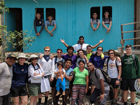 Students pose in front of one of the houses they painted in Lima, Peru.